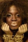 Ciérrese para arriba de los accessoaries modelo afroamericanos del oro que llevan, del maquillaje y del pelo rizado haciendo los  Fotografía de archivo