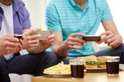 Ciérrese para arriba de los amigos con smartphone que representan la comida Fotografía de archivo