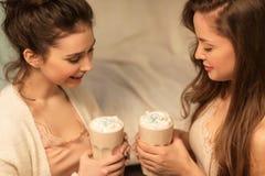Ciérrese para arriba de los amigos femeninos que beben cacao en casa Imagenes de archivo
