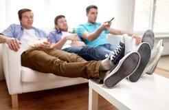 Ciérrese para arriba de los amigos masculinos que ven la TV en casa Foto de archivo