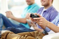 Ciérrese para arriba de los amigos que juegan a los videojuegos en casa Fotos de archivo libres de regalías