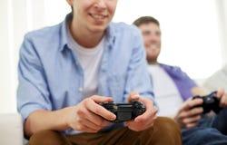 Ciérrese para arriba de los amigos que juegan a los videojuegos en casa imagen de archivo libre de regalías