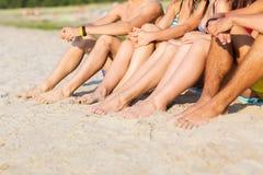 Ciérrese para arriba de los amigos que se sientan en la playa del verano Fotos de archivo
