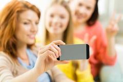 Ciérrese para arriba de los amigos que toman el selfie con smartphone Foto de archivo libre de regalías