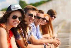 Ciérrese para arriba de los amigos sonrientes que se sientan en la calle de la ciudad Fotos de archivo libres de regalías