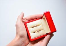 Ciérrese para arriba de los anillos de bodas en caja roja en manos imágenes de archivo libres de regalías