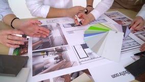 Ciérrese para arriba de los arquitectos que discuten plan junto en el escritorio con los modelos almacen de metraje de vídeo