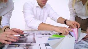 Ciérrese para arriba de los arquitectos que discuten plan junto en el escritorio con los modelos almacen de video