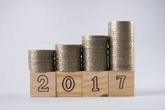 Ciérrese para arriba de los bloques número de madera 2017 con las monedas de plata apiladas en bloque de madera Imágenes de archivo libres de regalías