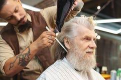 Ciérrese para arriba de los brazos tatuados que usando hairdryer Fotografía de archivo libre de regalías