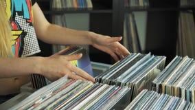 Ciérrese para arriba de los compradores que compran discos de vinilo almacen de metraje de vídeo