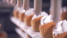 Ciérrese para arriba de los conos de la oblea que consiguen llenados de la sustancia blanca para el helado metrajes