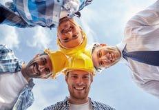 Ciérrese para arriba de los constructores que llevan los cascos de protección en círculo fotografía de archivo