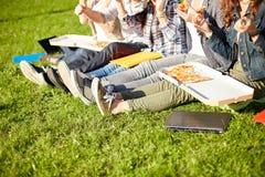 Ciérrese para arriba de los estudiantes adolescentes que comen la pizza en hierba Imagenes de archivo