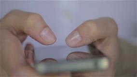 Ciérrese para arriba de los fingeres blancos del vestido de la mujer joven que mecanografían en su smartphone