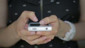 Ciérrese para arriba de los fingeres del vestido del negro de la mujer joven que mecanografían en su smartphone almacen de video