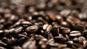 Ciérrese para arriba de los granos de café que giran metrajes