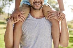 Ciérrese para arriba de los hombros de Carrying Son On del padre en parque imagenes de archivo