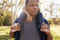 Ciérrese para arriba de los hombros de Carrying Son On del padre que caminan en parque fotografía de archivo libre de regalías