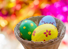 Ciérrese para arriba de los huevos de Pascua coloreados en cesta Imagen de archivo libre de regalías