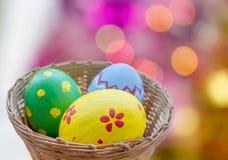 Ciérrese para arriba de los huevos de Pascua coloreados en cesta Imágenes de archivo libres de regalías