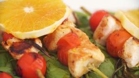 Ciérrese para arriba de los kebabs del pollo servidos con la cereza y el romero del tomate en el sartén metrajes