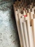 Ciérrese para arriba de los lápices idénticos del grafito y de un diverso cr rojo Foto de archivo libre de regalías