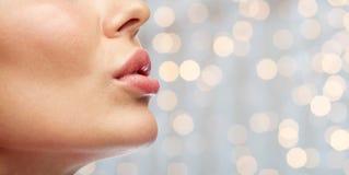 Ciérrese para arriba de los labios de la mujer joven sobre luces de los días de fiesta Foto de archivo libre de regalías