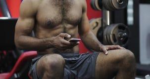 Ciérrese para arriba de los músculos desnudos de un hombre negro en un gimnasio almacen de video