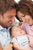 Ciérrese para arriba de los padres que abrazan al bebé recién nacido en H Fotos de archivo libres de regalías
