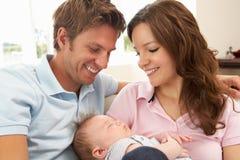 Ciérrese para arriba de los padres que abrazan al bebé recién nacido en H Foto de archivo libre de regalías