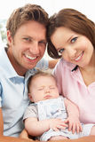 Ciérrese para arriba de los padres que abrazan al bebé recién nacido en H Imagenes de archivo
