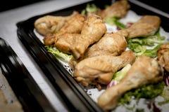 Ciérrese para arriba de los palillos del tambor del pollo asado en una comida fría en una bandeja con imagen de archivo