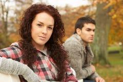 Ciérrese para arriba de los pares adolescentes que se sientan en banco Imagen de archivo libre de regalías