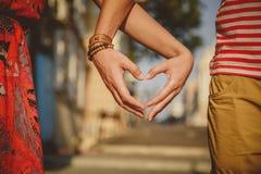 Ciérrese para arriba de los pares cariñosos que hacen forma del corazón con las manos en la calle de la ciudad verano Foto de archivo libre de regalías
