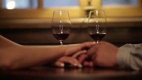 Ciérrese para arriba de los pares cariñosos que llevan a cabo las manos durante cena romántica Vidrios de vino rojo en fondo metrajes