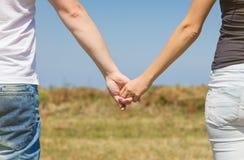 Ciérrese para arriba de los pares del amor que llevan a cabo las manos al aire libre Fotografía de archivo libre de regalías