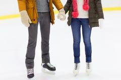 Ciérrese para arriba de los pares felices que patinan en pista de hielo Fotografía de archivo