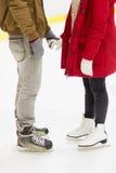 Ciérrese para arriba de los pares felices que patinan en pista de hielo Imágenes de archivo libres de regalías