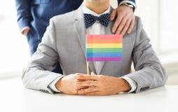 Ciérrese para arriba de los pares gay masculinos que sostienen la bandera del arco iris Imagen de archivo
