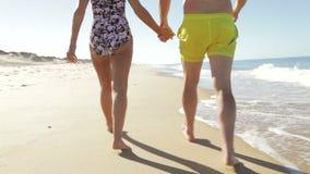 Ciérrese para arriba de los pares mayores que llevan a cabo las manos que caminan a lo largo de la playa almacen de video