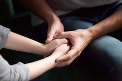 Ciérrese para arriba de los pares que llevan a cabo las manos, dando la ayuda psicológica c fotos de archivo