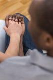 Ciérrese para arriba de los pares que llevan a cabo las manos mientras que se sienta Imagen de archivo