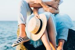 Ciérrese para arriba de los pares que se sientan en la piedra cerca del mar o del océano Foto de las manos que abrazan y que sost fotografía de archivo libre de regalías
