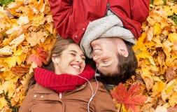 Ciérrese para arriba de los pares sonrientes que mienten en parque del otoño Foto de archivo