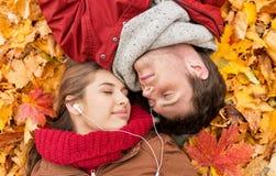 Ciérrese para arriba de los pares sonrientes que mienten en parque del otoño Fotografía de archivo libre de regalías