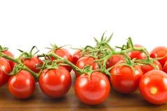 Ciérrese para arriba de los pequeños tomates de cereza rojos en una superficie de madera y un fondo blanco Fotografía de archivo libre de regalías