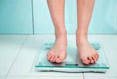 Ciérrese para arriba de los pies de la mujer que pesan en cuarto de baño imagen de archivo