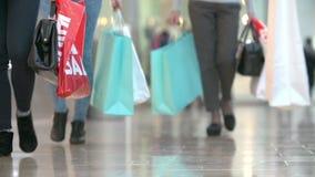 Ciérrese para arriba de los pies del comprador que llevan bolsos en alameda de compras