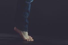 Ciérrese para arriba de los pies desnudos que se colocan en piso oscuro Fotografía de archivo